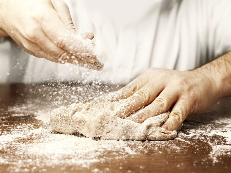 Close-up of a baker working with dough