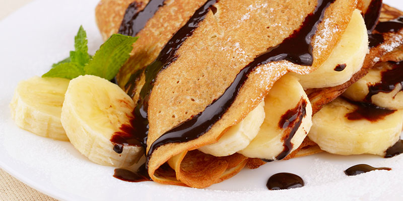 Close-up of crepes with banana and chocolate sauce